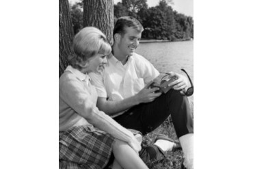 Young couple sitting at side of pond Poster Print (18 x 24)
