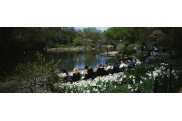 Group of people sitting on benches near a pond, Central Park,