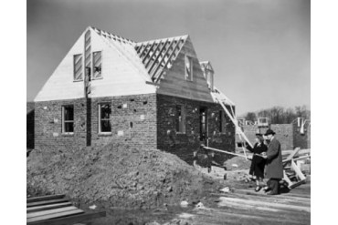 Man and woman looking at a house under construction Poster Print (24 x 36)