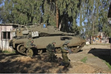 An Israel Defense Force Merkava Mark II battle tank with infantry forces.